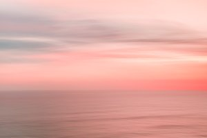 Blurred sunset sky and ocean in pink