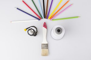 Desk of an artist with lots stationery objects. Studio shot on white background, and funny face
