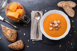 Pumpkin soup in a white bowl on table