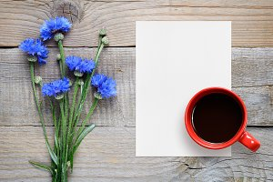 Cornflowers, paper and coffee cup