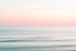 Blurred pink sunrise sky and ocean