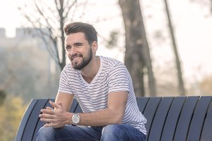 man sitting bench, smiling, happy