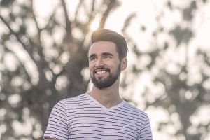 man smiling looking sideways sunny