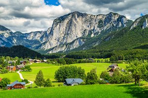 Green fields with alpine village