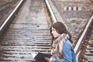 Young girl reading on the railway