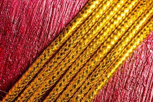 Gold thread on red texture background. Christmas gift, close up.