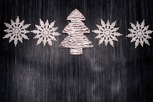 Christmas snowflakes and christmas tree on a wooden background.