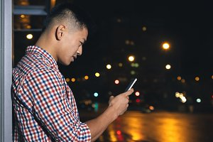 Young man using mobile in the street