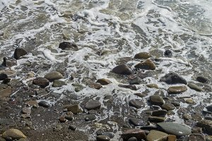 Coastal pebbles in the surf. Crimea.