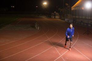 Runner running tracks night dark