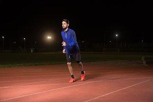 Man runner running tracks, night