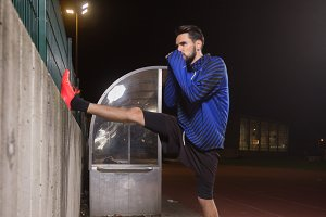 Athlete man stretching cold winter