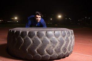 Man athlete tire exercise, night