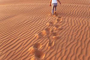 Baby - girl running in the desert.
