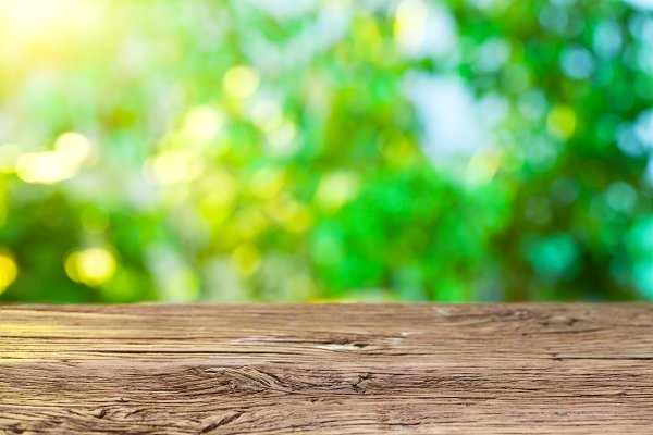 Wooden desk and blurred foliage