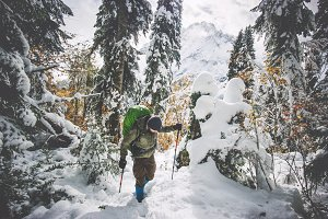 Man Traveler hiking in winter forest