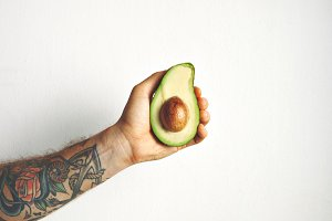 Man's arm with half of avocado