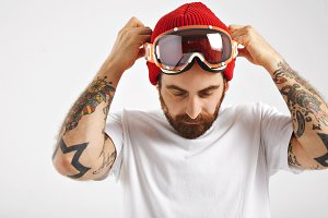 Snowboarder in white t-shirt putting on goggles