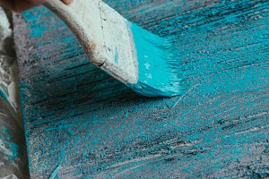 closeup hand use brush paint white blue on wood surface