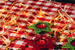 candle on red checkered tablecloths and garland