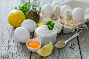 Mayonnaise sauce and ingredients on wood background