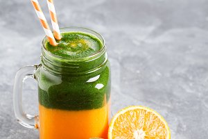 Layered healthy smoothie with spinach, kiwi, orange and mango