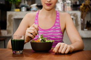 Attractive fitness woman is eating salad with healthy glass of juice - Fitness and Diet concept