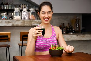 Attractive Caucasian fitness woman is eating salad with healthy glass of juice - Fitness and Diet concept