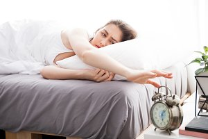 Woman reaching out hands and trying to turn off alarm in the morning