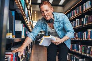 Young man at bookshelf
