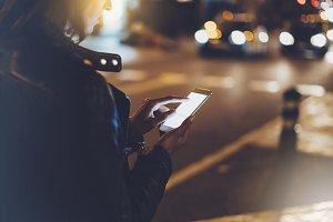 Girl holding phone in night city