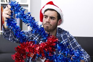 young man with santa Hat decorating the House with Christmas decorations