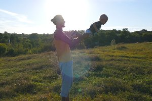 Young father playing with his child at nature. Dad holding his son's legs and throws it outdoor. Happy family spending time together outside at meadow. Beautiful landscape at background. Close up