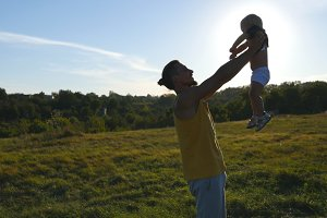 Young father playing with his little son outdoor. Dad lifting up his child at nature. Happy family spending time together outside at meadow. Beautiful landscape at background. Close up