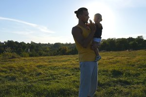 Young father holds on hands his son in the meadow at nature at sunny summer day. Dad and little boy hugging outdoor and giving five to each other. Beautiful landscape at background. Close up