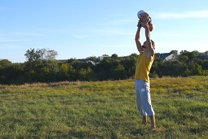 Young father throwing up his little son outdoor. Dad playing with his child at nature. Happy family spending time together outside at meadow. Beautiful landscape at background. Close up