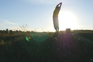 Silhouette of sporty man standing at yoga pose outdoor. Yogi practicing yoga moves and positions in nature. Beautiful sky and sun as background. Healthy active lifestyle