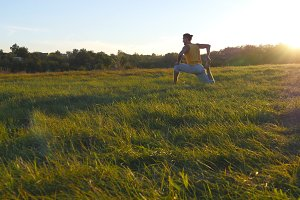 Young man sitting at green grass in the meadow and doing yoga exercise. Muscular guy stretching his body at nature. Training outdoor at sunny day. Beautiful landscape at background. Close up