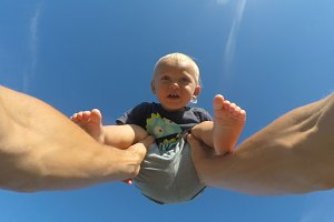 Hands of father lifts his little son on a sunny day. Dad playing with cute baby at nature. Blue sky at background. Family spends time together outdoor. POV - point of view. Close up