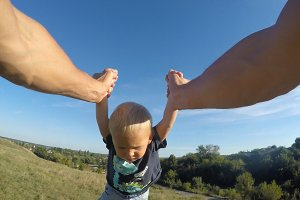 Father spinning his little son in a meadow on a sunny day. Dad rotate cute baby around at nature. Boy hold hands of parent. Family spends time together outdoor. POV - point of view. Close up