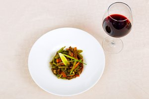 Meat dish with vegetables in a plate and a glass of red wine