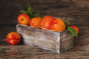 Fresh apricots in small wooden box, selective focus, top view
