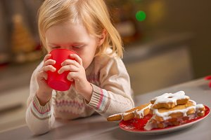 Baby drinking milk with christmas cookies in kitchen