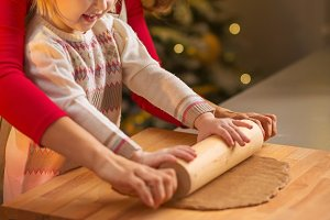 Smiling mother and baby rolling pin dough in christmas decorated kitchen