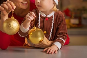 Closeup on mother and baby holding christmas balls