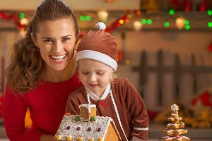 Smiling mother and baby decorating christmas cookie house in kitchen
