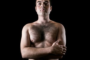Man with hairy chest isolated on black background