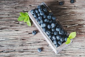 fresh blueberries and blueberry in a wooden box, selective focus