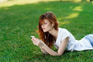 girl on grass with phone