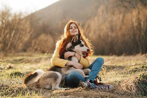 Young girl hugging husky dog